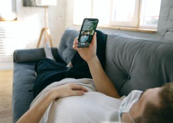 Muž s mobilním telefon leží na gauči