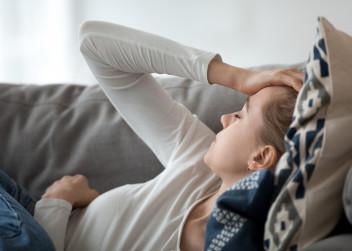Unavená žena leží na gauči