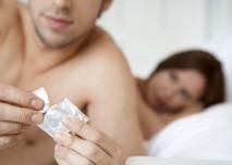 muž vytahuje kondom z obalu před pohlavním styekm